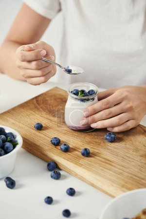 cropped shot of woman at tabletop with yogurt with fresh blueberries for breakfast on wooden cutting board
