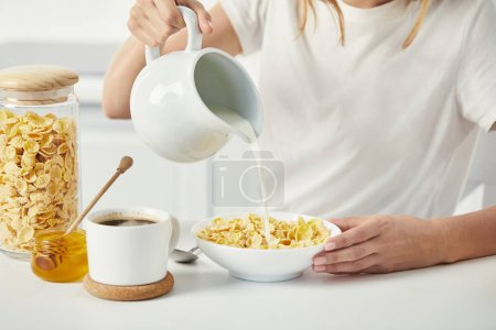 Photo for Partial view of woman pouring milk into bowl with corn flakes during breakfast at home - Royalty Free Image