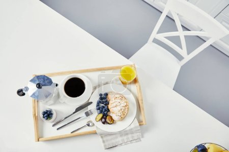 top view of croissant with fresh blueberries and plum pieces, glass of juice, cup of coffee and yogurt on wooden tray for breakfast on white tabletop