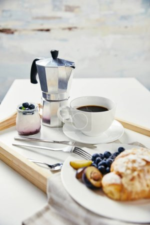 close up view of tasty breakfast with yogurt and cup of coffee on wooden tray on white surface