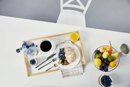 top view of croissant with fresh blueberries and plum pieces, glass of juice, cup of coffee and yogurt for breakfast on wooden tray on white tabletop