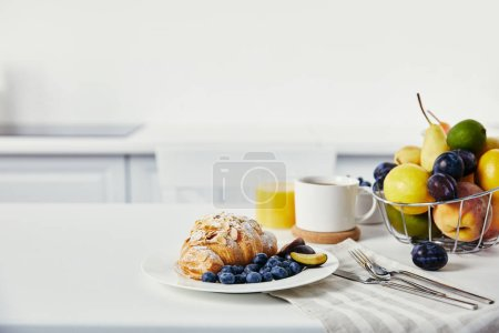 close up view of tasty breakfast with croissant and cup of coffee on white surface