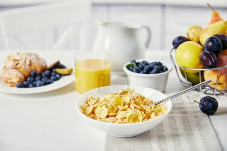 close up view of tasty breakfast with corn flakes and glass of juice on white surface