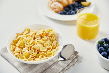 close up view of corn flakes in bowl, glass of juice and croissant with blueberries and plum pieces for breakfast on white tabletop