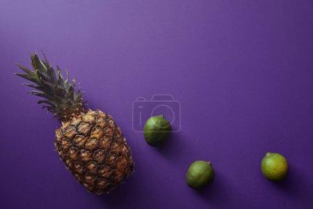 Photo pour Vue de dessus de l'ananas et des citrons verts sur la surface violette - image libre de droit