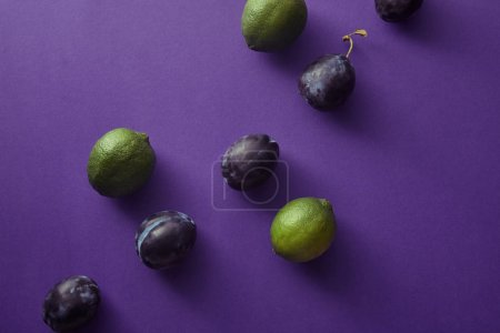 top view of plums and limes on violet surface