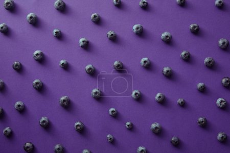 pattern of ripe blueberries on violet surface