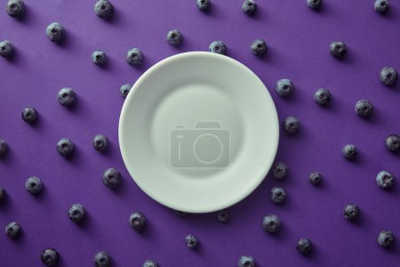top view of plate and blueberries on violet surface