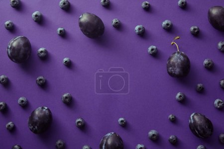 top view of blueberries and plums on violet surface