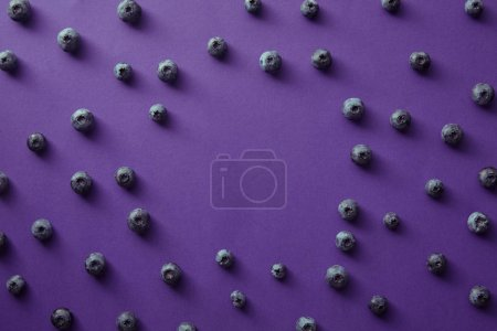 top view of circle of blueberries on violet surface