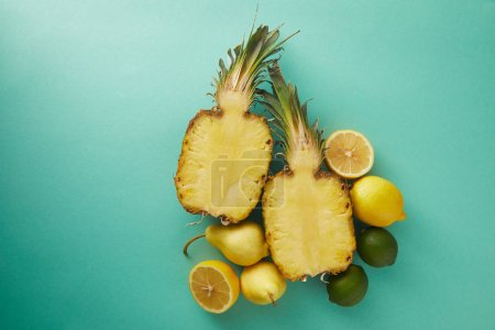 elevated view of cut pineapple, pears and lemons on turquoise surface