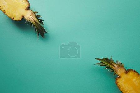 Photo pour Vue de dessus des ananas coupés sur surface turquoise - image libre de droit
