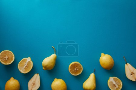 Photo for Top view of pears and lemons on blue surface - Royalty Free Image