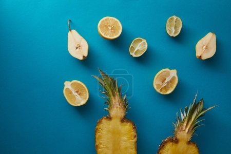 elevated view of ripe pineapple, pears and lemons on blue surface