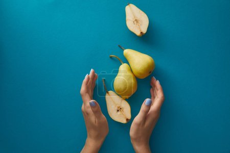 Photo for Cropped image of woman holding hands near pears above blue surface - Royalty Free Image