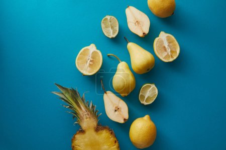 elevated view of pineapple, pears and lemons on blue surface