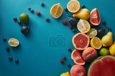 Photo for Elevated view of appetizing ripe fruits and berries on blue surface - Royalty Free Image