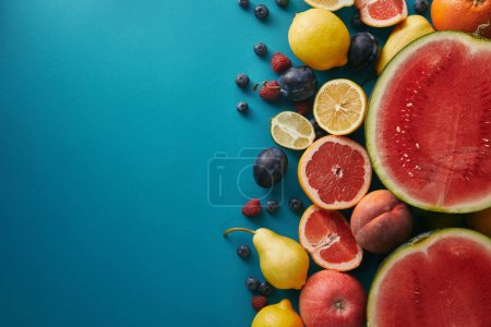 top view of grapefruits, lemons and berries on blue surface