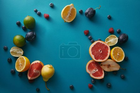 top view of organic ripe fruits and berries on blue surface