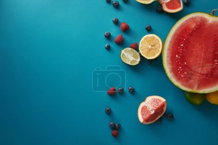 Photo for Top view of fruits and berries on blue surface - Royalty Free Image