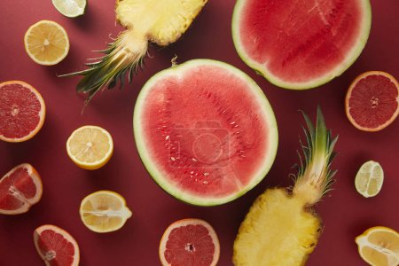 top view of appetizing raw fruits on red surface