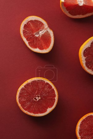 elevated view of cut grapefruits on red surface