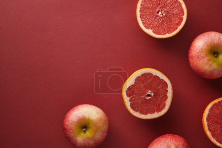 top view of grapefruits and apples on red surface