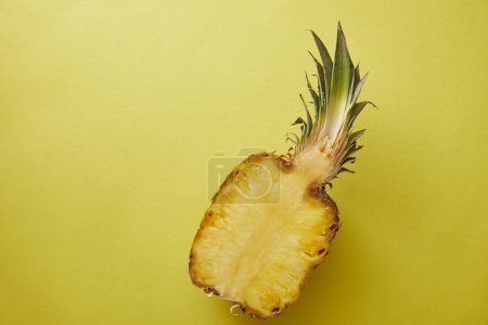 Photo for Top view of half of pineapple on yellow surface - Royalty Free Image