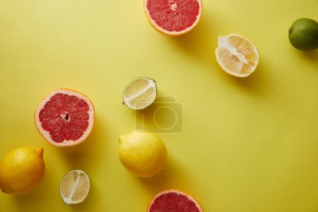 top view of grapefruits, lemons and limes on yellow surface
