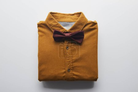 top view of brown shirt and bow tie on white