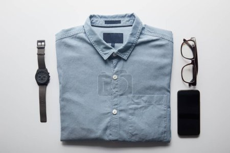 flat lay of shirt, smartphone and glasses isolated on white