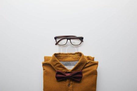 top view of brown shirt with bow tie and glasses isolated on white