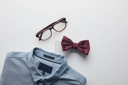top view of blue shirt, burgundy bow tie and glasses isolated on white