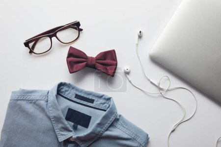 Photo for Top view of blue shirt, burgundy bow tie, glasses and laptop with earphones isolated on white - Royalty Free Image