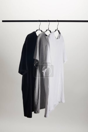 Photo for Black, grey and white shirts on hangers isolated on white - Royalty Free Image