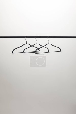 three empty hangers on stand isolated on white