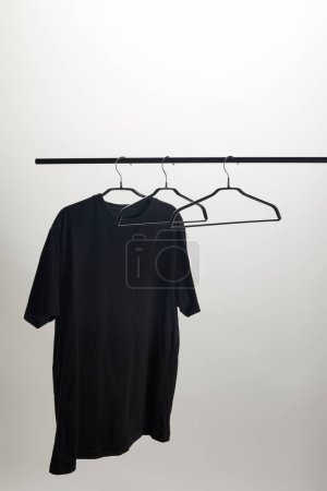 one black shirt and empty hangers on stand isolated on white