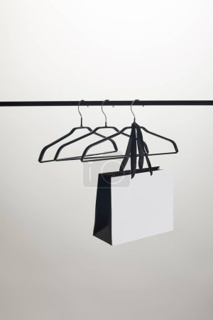 Photo for Shopping bag and empty hangers on stand isolated on white - Royalty Free Image