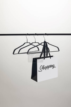 paper bag with word shopping and empty hangers on stand isolated on white