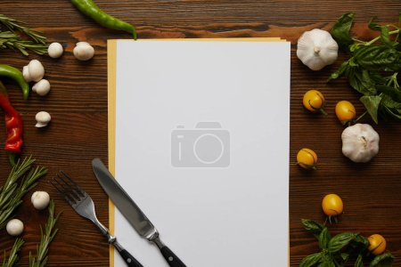 top view of blank card, cutlery and fresh vegetables on wooden surface
