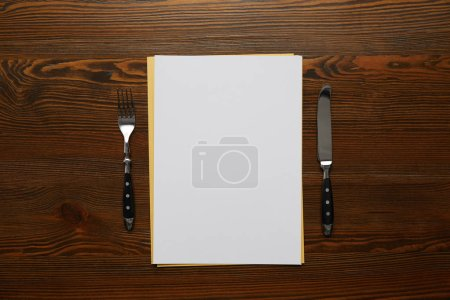 top view of blank card, fork and knife on wooden table