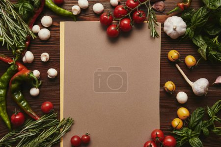top view of blank menu and fresh vegetables with herbs on wooden surface