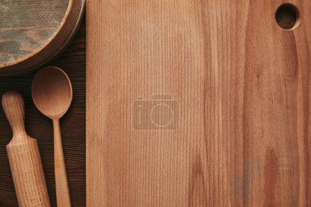 Photo for Top view of wooden cutting board, spoon, rolling pin and sieve on table - Royalty Free Image