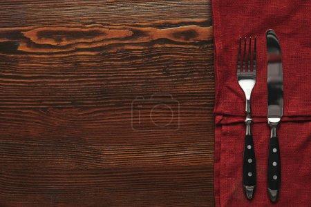 Photo pour Vue de dessus des fourchettes et des couteaux sur une nappe rouge foncée sur la table en bois - image libre de droit