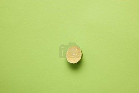 Photo pour Vue de dessus du citron vert mûr coupé en deux sur fond vert clair - image libre de droit