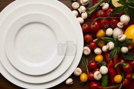 Foto de Vista superior de vacías ronda placas blancas y verduras frescas en la superficie de madera - Imagen libre de derechos