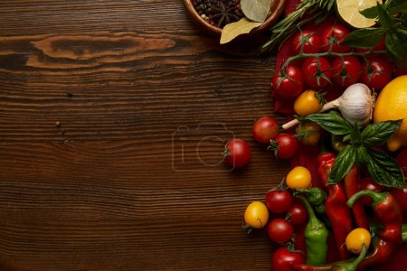 top view of fresh ripe vegetables and spices on wooden surface