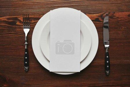 Ansicht der leeren Karte auf weißen Tellern mit Gabel und Messer auf Holztisch