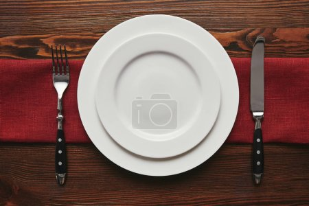 Photo for Top view of round empty white plates with fork and knife on wooden table - Royalty Free Image