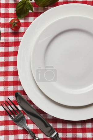 top view of empty white plates, cutlery and fresh basil with tomato on checkered tablecloth